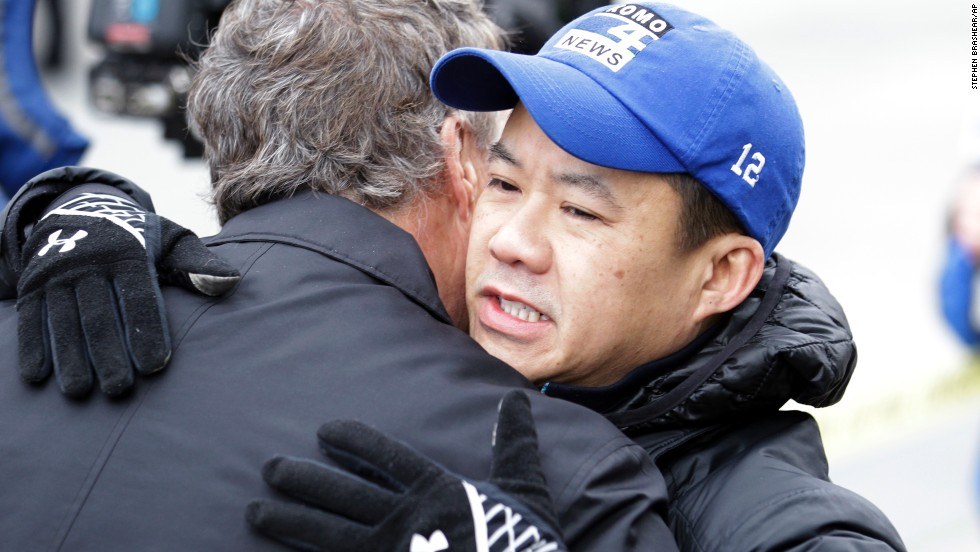 Norm Mah, assignment editor for CNN affiliate KOMO-TV, gets a hug as he works at the scene of the crash. The crash happened near the KOMO-TV studios, and the helicopter was used by both KOMO and KING, according to KING's website.