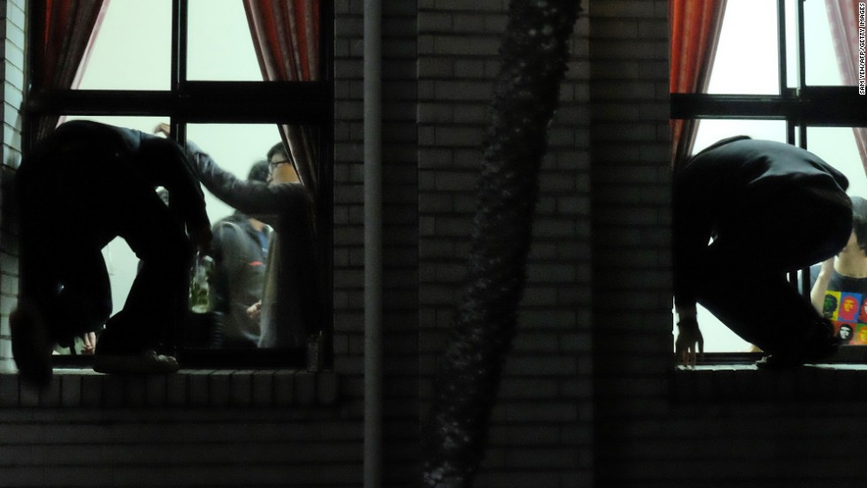 Protesters climb through the windows of the Legislature on March 19.