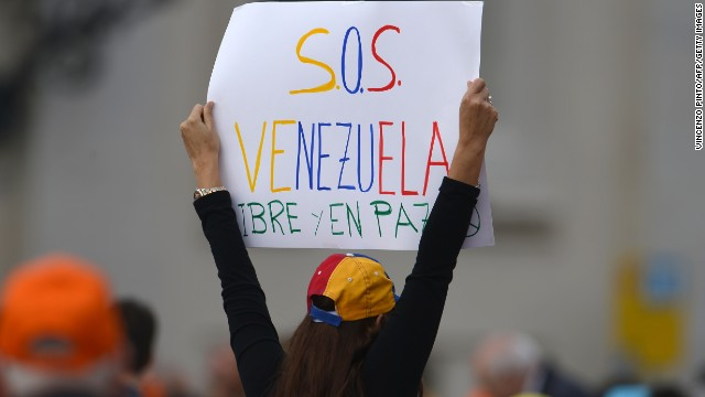 A woman holds a placard reading 'SOS Venezuela' before Pope Francis general audience at St Peter's square on March 19, 2014 at the Vatican. AFP PHOTO / VINCENZO PINTO (Photo credit should read VINCENZO PINTO/AFP/Getty Images)