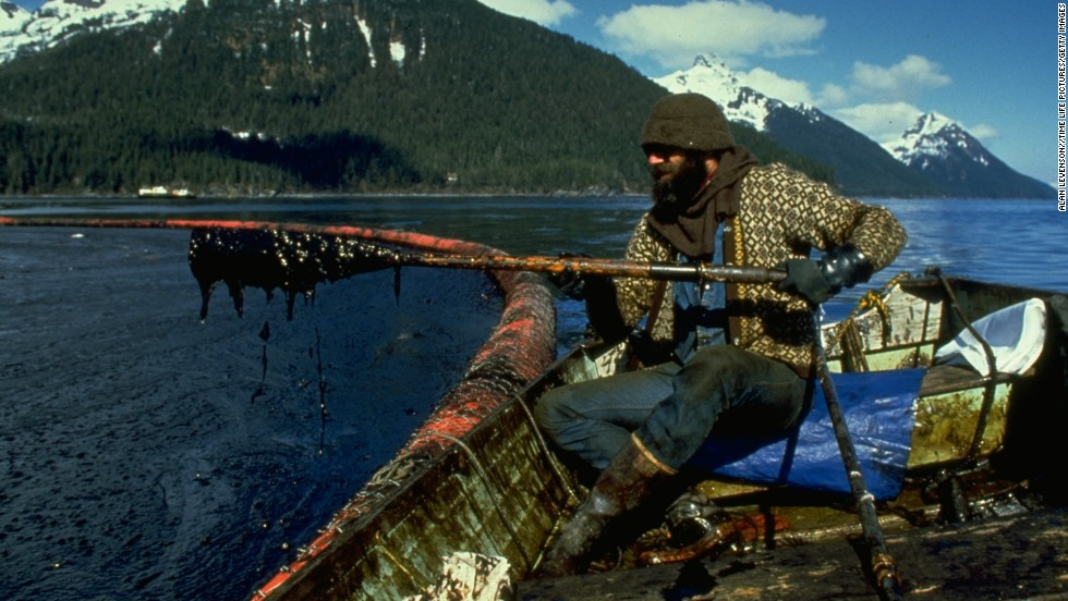 A cleanup worker checks gunk trapped by a floating boom in the Prince William Sound after the spill.