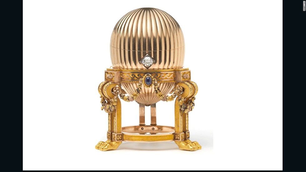 The 8.2-centimeter (3.2-inch) Faberge egg is on an elaborate gold stand supported by lion paw feet. Three sapphires suspend golden garlands around it, and a diamond acts as an opening mechanism.