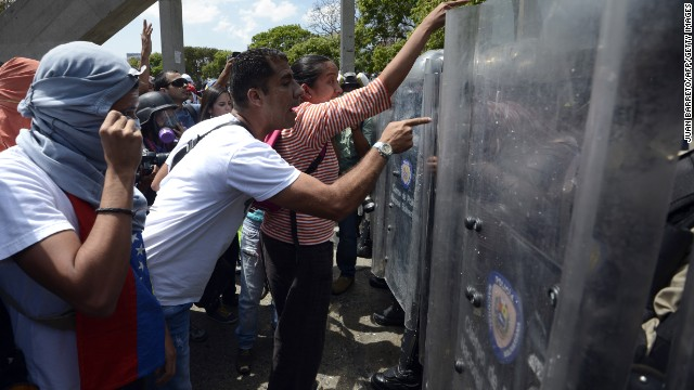 Anti-government activists confront the National Police during a protest against Venezuelan President Nicolas Maduro, in Caracas, on March 20, 2014. Venezuela upped pressure on the opposition Wednesday after weeks of protests, arresting two mayors including one in the town where they started and seeking a probe of a prominent anti-government lawmaker. Authorities said the death toll from the protests rose to at least 30 after a policeman died trying to break up a protest in the western city of San Cristobal, where the demos began February 4. AFP PHOTO/JUAN BARRETO (Photo credit should read JUAN BARRETO/AFP/Getty Images)