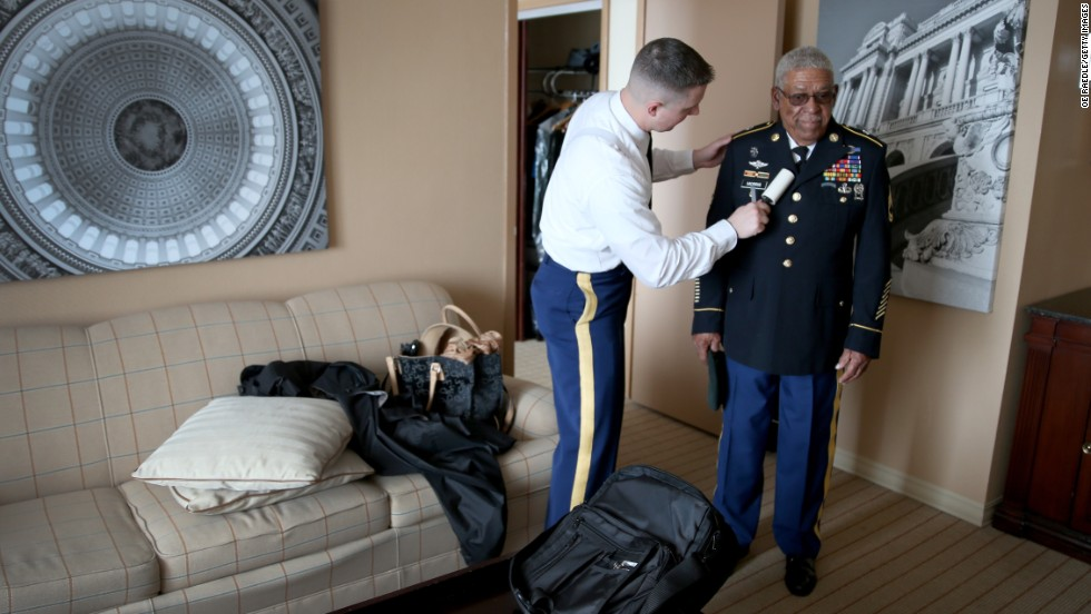 "U.S. Army Staff Sgt. Christopher Schneider uses a lint roller on the uniform of retired Army Sgt. 1st Class Melvin Morris before Morris' trip to the White House on Tuesday, March 18. Morris was among <a href=""http://www.cnn.com/2014/03/18/politics/gallery/medal-of-honor-2014/index.html"">24 soldiers who received the Medal of Honor</a>, the country's highest military award, for courageous actions in Vietnam, Korea and World War II."
