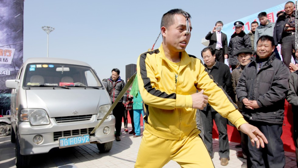 Stuntman Zhang Yilong pulls a van by his nostrils during an auto show in Zhoukou, China, on Friday, March 14.