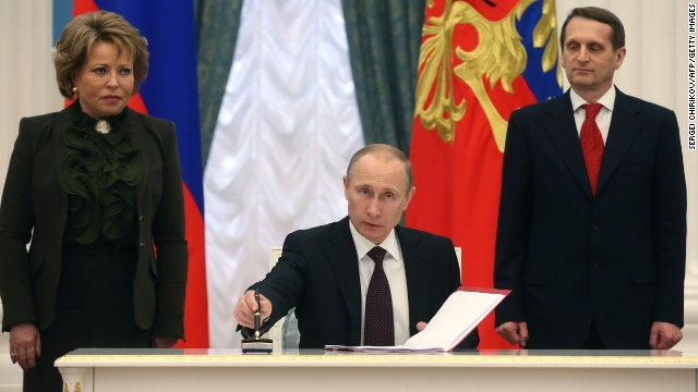 Russia's President Vladimir Putin (C) signs a law on ratification of a treaty making Crimea part of Russia, during a ceremony in the Kremlin in Moscow March 21, 2014, with Valentina Matviyenko (L), the speaker of the upper house of Russian parliament, the Federation Council, and Sergei Naryshkin (R), the speaker of parliament's lower house, the State Duma, attending the ceremony. Putin said today Moscow would hold off on further reciprocal sanctions against the United States, after Washington introduced punitive measures against his close allies over the Ukraine crisis.