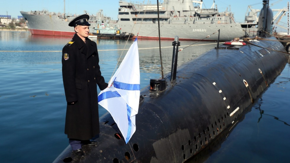 A Russian sailor holds the Russian Navy's St. Andrew's flag while standing on the bow of the surrendered Ukrainian submarine Zaporozhye on March 22 in Sevastopol.