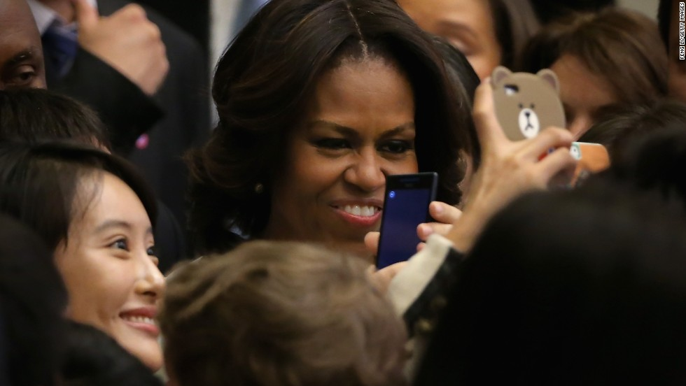 A Chinese student takes pictures with her phone beside Obama after the first lady spoke at the Stanford Center at Peking University.