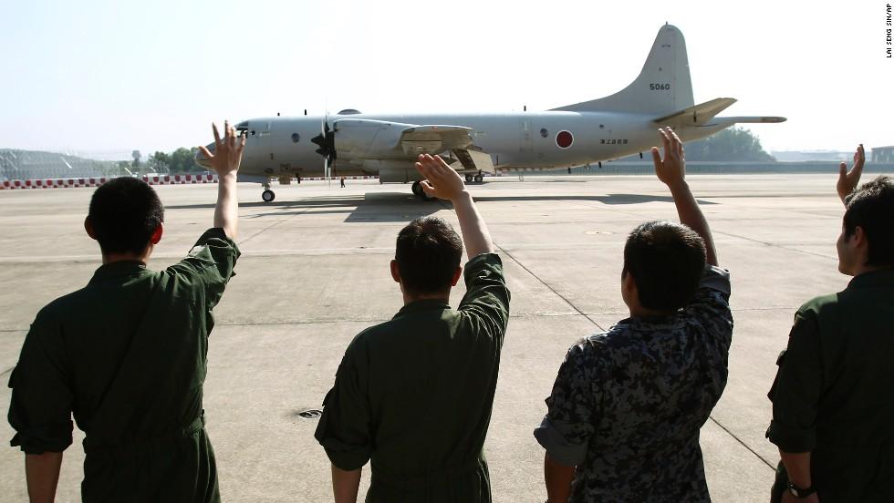 Miembros de la Fuerza de Defensa Marítima de Japón despiden a un avión que despega de la base aérea de Malasia en dirección a Australia para unirse a las labores de búsqueda.