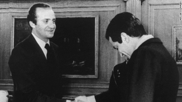 Outgoing Prime Minister Adolfo Suarez (R) bows his head to Spanish King Juan Carlos, 24 February 1981, at the Royal Palace, in Madrid, after Suarez was released by insurgent rebels who had held him and 350 members of Parliament hostage for 17 hours. (Photo credit should read -/AFP/Getty Images)