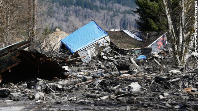 A destroyed home is seen attop the mud and debris on Highway 530 near Oso, Washington, on March 23, where a landslide wiped out several homes, blocked the road and the Stillaguamish River.  At least four people have been killed in the landslide.