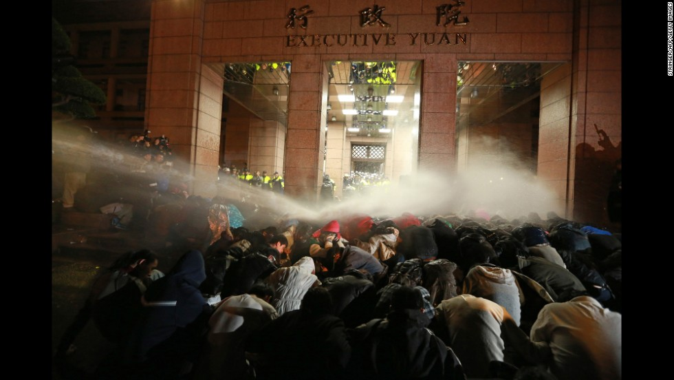 Protesters are sprayed with a water cannon during a demonstration outside the Executive Yuan building in Taipei on March 24.