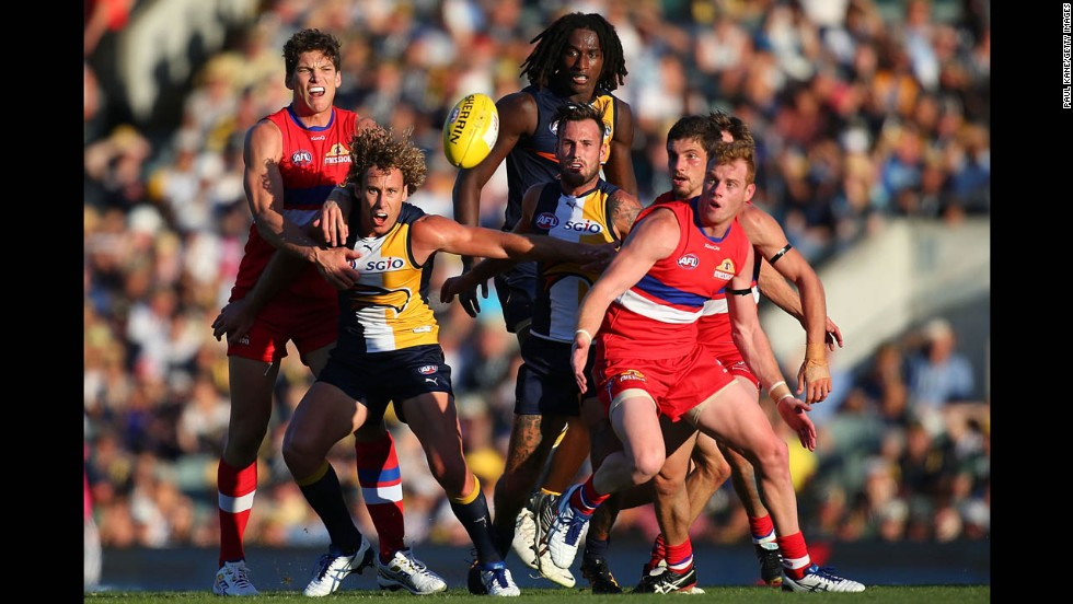 Players of the West Coast Eagles and the Western Bulldogs eye the ball during an Australian rules football match Sunday, March 23, in Perth, Australia.