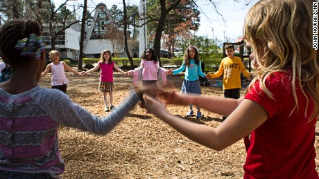 Students join hands while playing a game outside.