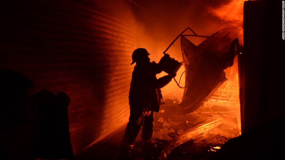 A firefighter tries to douse the fire.