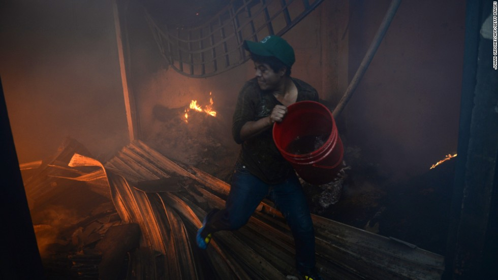 A shopkeeper tries to throw a bucket of water on the fire.