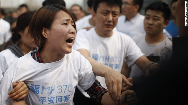A relative of passengers on missing Malaysia Airlines flight MH370 yells at a security personnel while she attends a protest outside the Malaysian embassy in Beijing on March 25, 2014.