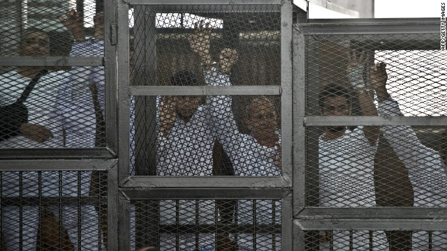Australian journalist Peter Greste (C) of Al-Jazeera and his colleagues stand inside the defendants cage during their trial for allegedly supporting the Muslim Brotherhood at Cairo's Tora prison on March 5, 2014.