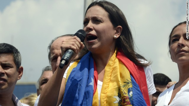 Dismissed opposition deputy Maria Corina Machado (C), Peruvian deputies Cecilia Chacon (R) and Luis Galarreta (L) take part in a protest against the Venezuelan government in Caracas on March 26, 2014. On Monday, National Assembly president Diosdado Cabello announced that a prominent opposition deputy, Maria Corina Machado, had lost her seat and parliamentary immunity, and could be arrested at any time. AFP PHOTO / JUAN BARRETO (Photo credit should read JUAN BARRETO/AFP/Getty Images)