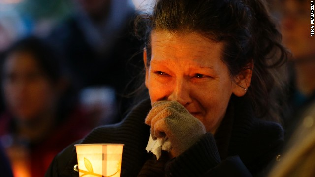 Teresa Welter cries as she holds a candle at a vigil for victims of the nearby landslide in Arlington, Washington, on Tuesday, March 25.