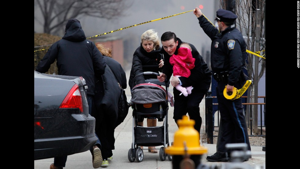 A police officer holds up caution tape as a man, woman and child run from the scene on March 26.