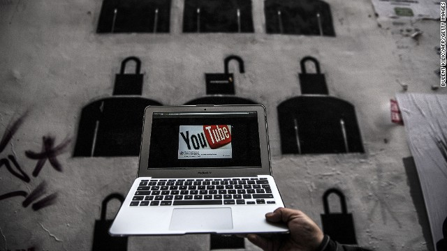 A laptop computer showing Youtube's logo on its screen is held in front of graffiti on March 27, 2014 in Istanbul.