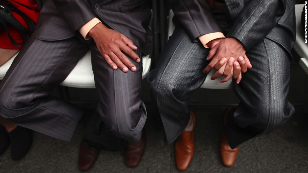 A same-sex couple holds hands during a mass wedding in Mexico City on Friday, March 21.