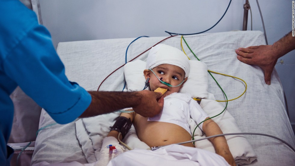 """Abuzar Ahmad is fed by hospital staff Monday, March 24, after he <a href=""""http://www.cnn.com/2014/03/21/world/asia/afghanistan-violence/index.html"""">survived an attack</a> at a hotel in Kabul, Afghanistan. His father, Agence France-Presse reporter Sardar Ahmad, was killed in the attack, as were his mother, his siblings and several other civilians."""