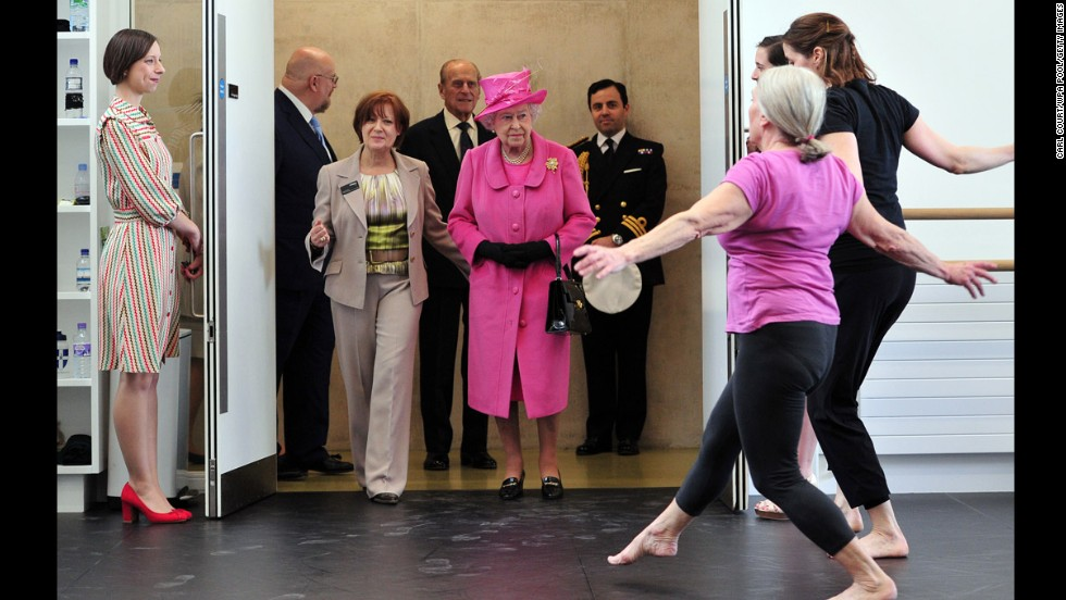 Britain's Queen Elizabeth II, wearing the pink hat, watches dancers perform Friday, March 21, during a visit to the Rambert Dance Company in London.