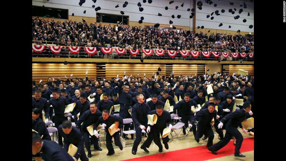 Graduating cadets toss their caps in the air Saturday, March 22, during the commencement ceremony at Japan's National Defense Academy in Yokosuka.