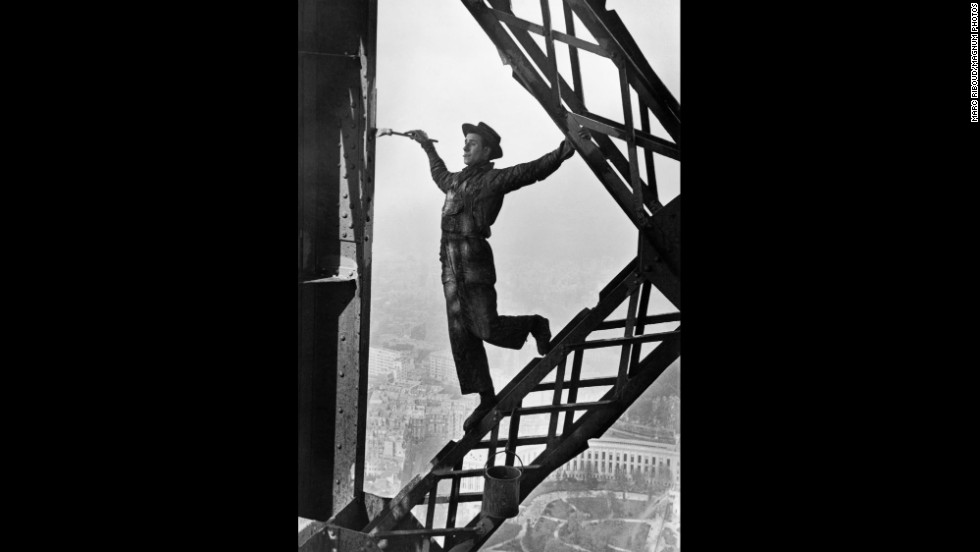 A man named Zazou paints the Eiffel Tower in 1953. The tower is repainted every seven years, necessitating 60 metric tons of paint.