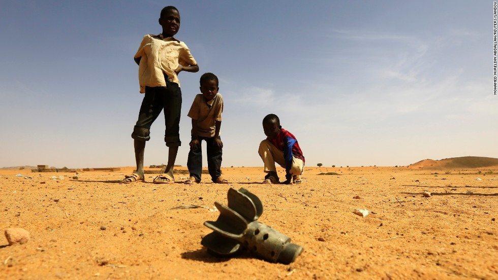 Children look at the fin of a mortar projectile that was found at the Al-Abassi displacement camp on Tuesday, March 25, after an attack by rebels in North Darfur, Sudan.