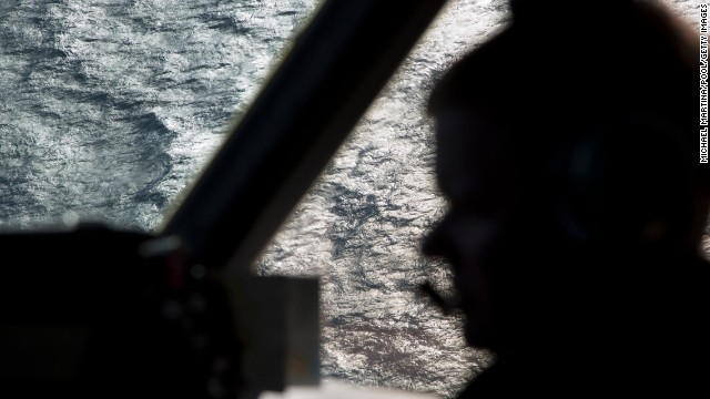 A member of the Royal Austrain Air Force is silhouetted against the southern Indian Ocean during a search for the missing jet on Thursday, March 27.
