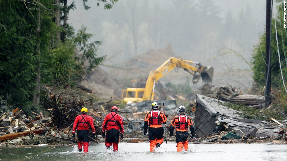 Search-and-rescue workers wade through water covering a highway near Darrington on Thursday, March 27. The landslide left buildings covered in up to 40 feet of mud.