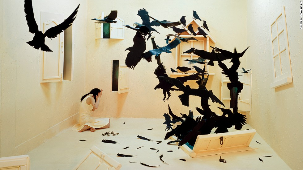 "Fears and negative feelings are represented as menacing crows bursting through a door in the floor. ""For me large birds are threatening, and the image of their feathers, beak, and curved talons is frightening,"" says Lee. The doors represent future changes and challenges that the artist will have to go through."