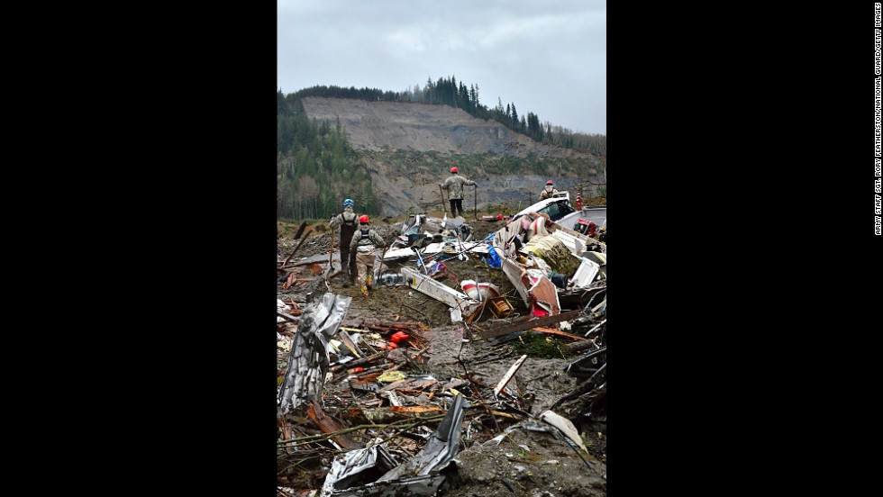 Air National Guard members look out at the hill where the landslide originated while they search through debris March 29 in Oso.