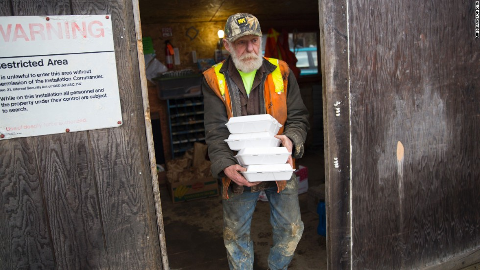 Skaglund Quarry worker Warren Tollenaar carries meals donated by concerned community members. He is among the workers who are grinding up rock so trucks and rescue equipment can get through the landslide debris zone. He, like all of the volunteers, aren't getting paid. They do it, he says, because that's what has to be done.