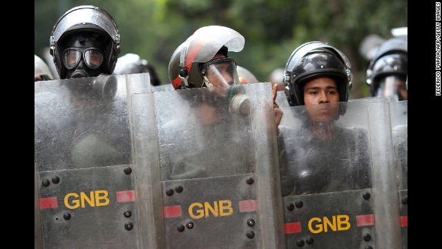 Officers stand guard during an anti-government march in Caracas on Saturday, March 29.