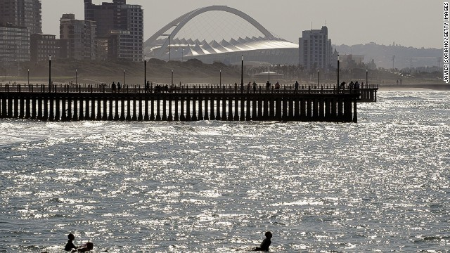 Surfers take to the Indian Ocean, with the Moses Mabhida Stadium - which hosted 2010 World Cup matches - in the background.