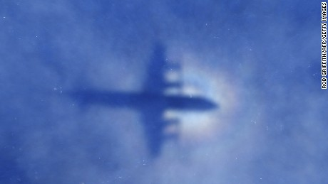 This shadow of a Royal New Zealand Air Force P3 Orion aircraft is seen on low cloud cover while it searches for missing Malaysia Airlines flight MH370, over the Indian Ocean on March 31, 2014. No time limit will be imposed on the search for MH370 because the world deserves to know what happened, Australian Prime MinisterTony Abbott said, as a ship equipped to locate the plane's 'black box' prepared to set sail. AFP PHOTO / POOL / Rob GRIFFITH (Photo credit should read ROB GRIFFITH/AFP/Getty Images)