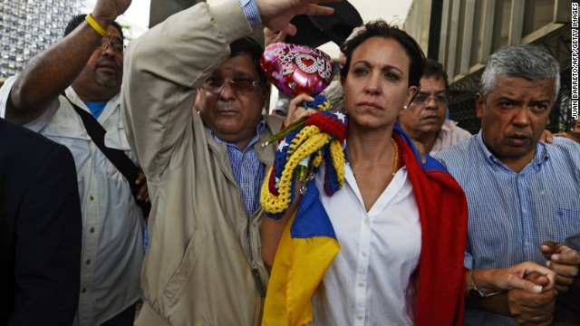 Venezuelan opposition lawmaker Maria Corina Machado (2-R) heads to an administrative office dependent on the National Assembly, in Caracas on April 1, 2014. In a direct challenge to President Nicolas Maduro, prominent opposition politician Machado vowed to take her seat in the National Assembly despite her ouster by the Supreme Court. The head of the legislative body had ordered Machado expelled and her parliamentary immunity stripped last week after she tried to speak before the Organization of American States about her country's crisis. AFP PHOTO/JUAN BARRETO (Photo credit should read JUAN BARRETO/AFP/Getty Images)