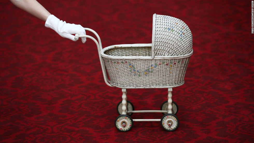 A 1928 wicker toy pram belonging to the Queen is displayed.