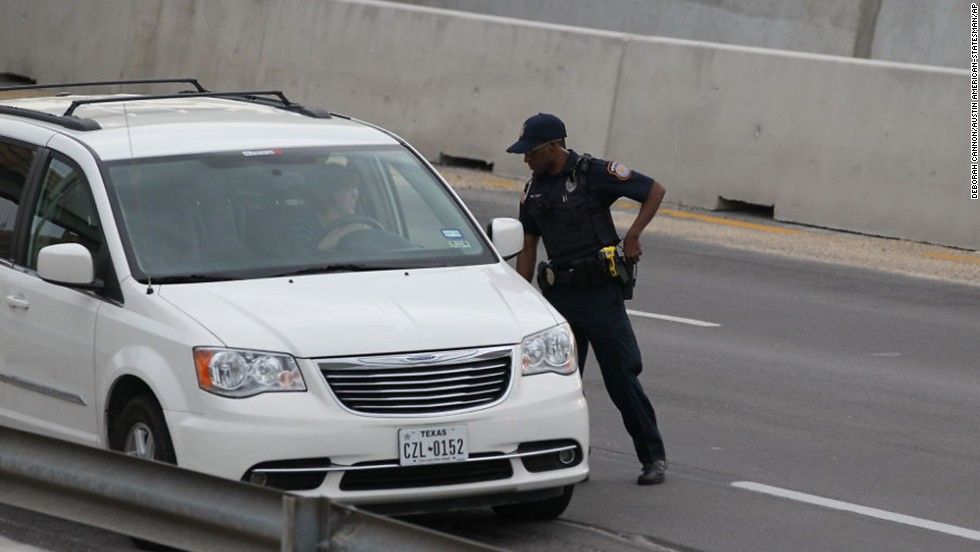 A police officer checks drivers' IDs outside the main gate at Fort Hood.