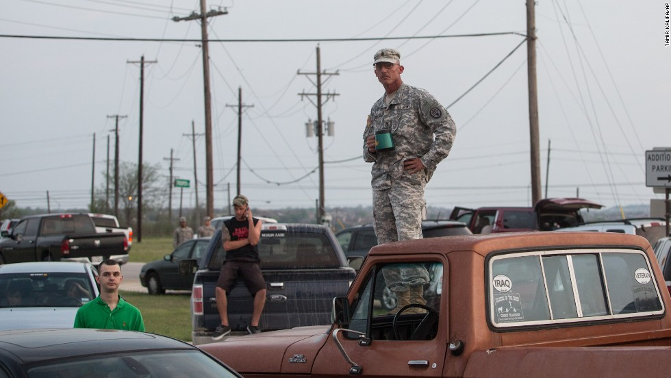 Military personnel and civilians wait outside Fort Hood for updates on the situation.