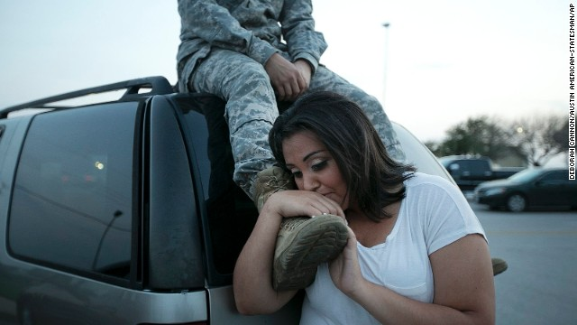 Lucy Hamlin leans on her husband's foot, Specialist Timothy Hamlin, as they wait to be allowed back onto Fort Hood, Texas, where they reside on Wednesday, April 2, 2014. A shooting occurred on the base with at least four dead and 14 injured according to the officials. Deborah Cannon/Austin American-Statesman/AP