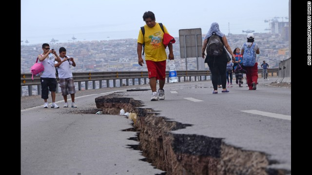 People walk along a cracked road in Iquique, Chile, on Wednesday, April 2.