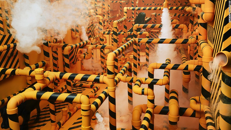 "The artist tried to express her difficulties in communication with some people through a maze of pipes. ""I used yellow and black, as those colors are often seen on signs which warn of danger,"" she says. The black dog in the corner of the picture represents a person who was troubling Lee at the time."