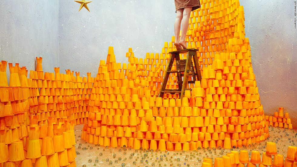 "In this image, over 2,000 hand-painted paper cups are stacked together as bricks of a fragile castle. Lee explains: ""I wanted to express the process of heading toward your desire, along with the effort it takes to achieve your dream, which is represented by the star."" The glass marbles spread on the floor symbolize fallen stars."