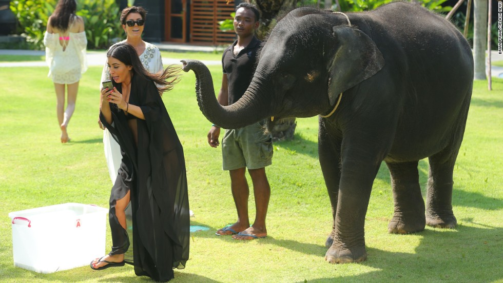 Kim Kardashian has her hair pulled by a baby elephant as she takes a selfie in Thailand on Monday, March 31.