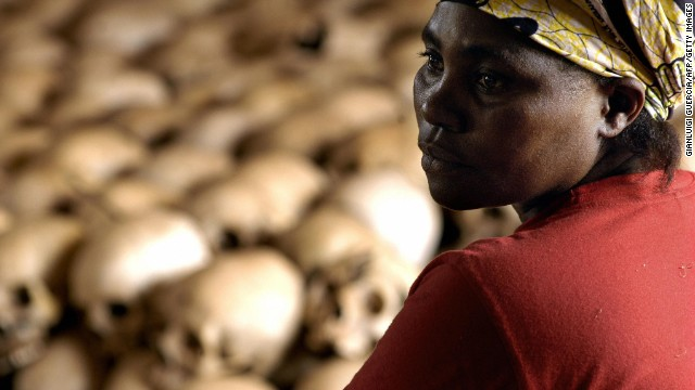 Genocide memorial site guardian, Danielle Nyirabazungu, rests 27 February 2004 close to the skulls of the people killed during the 1994 genocide in the church of Nyamata, Rwanda.