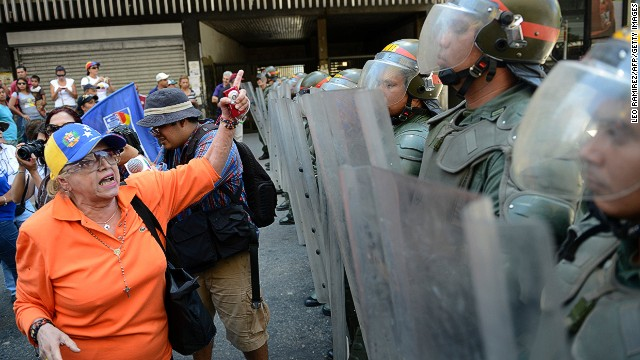 An opposition activist gestures in front of a line of National Guards in riot gear during a protest demanding to know the real situation of President Hugo Chavez's health, in Caracas on March 3, 2013.